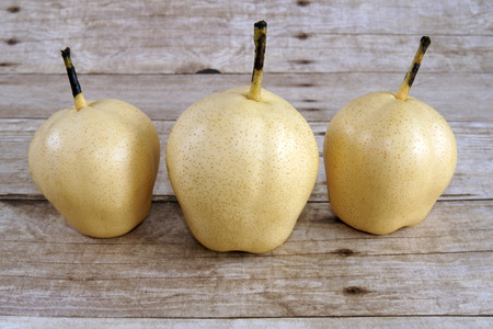 asian pear: Chinese Ya Pears on a wooden background Also known as Asian pear, Chinese pear, Korean pear, Japanese pear, Taiwan pear, and sand pear Stock Photo