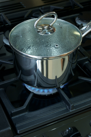 Saucepan on a gas cooker hob photo