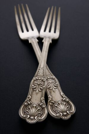 tarnish: Antique silver forks on a black background with selective focus Stock Photo
