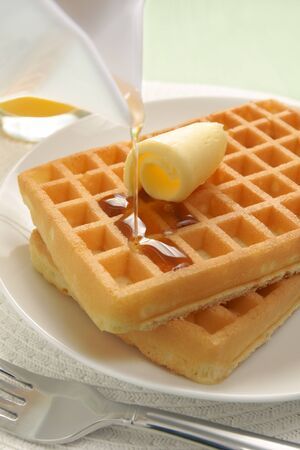 Pouring maple syrup over waffles