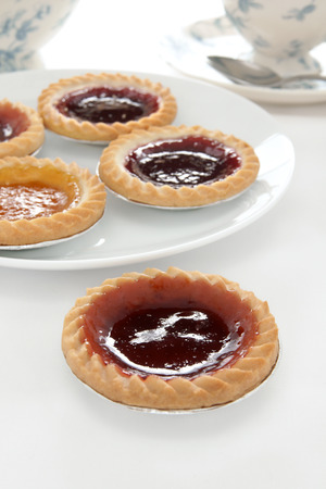 jam tarts: Jam tarts and afternoon tea on a white table cloth Stock Photo