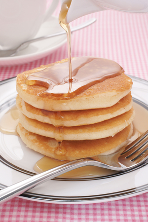 Pouring maple syrup on buttermilk pancakes photo