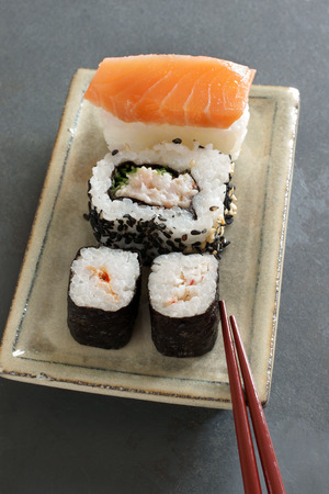laquered: Maki, Uramaki   nigiri sushi made with salmon and prawn on a Japanese ceramic dish with laquered chopsticks, natural slate background Stock Photo