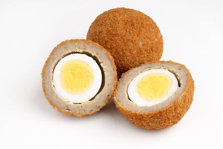 boiled eggs: Scotch eggs a hard boiled egg wrapped in pork sausage meat and breadcrumbs studio isolated