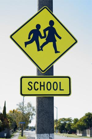 スクール ゾーンに入っている学校交差の標識の警告ドライバー 写真素材
