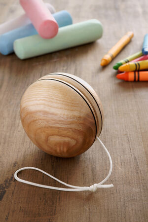 yo: An old fashioned style wooden yoyo with chalks and wax crayons a retro childhood concept