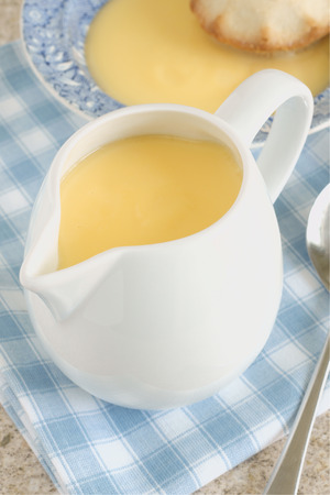 jugs: Custard a popular dessert sauce based on a cooked mixture of milk or cream and egg yolk Stock Photo