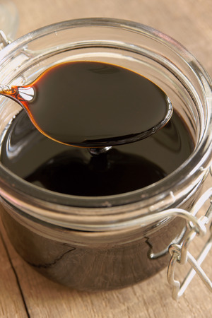 syrup: Black Treacle or molasses selective focus on the spoon Stock Photo