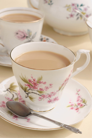 mismatch: Afternoon tea served in vintage floral mismatched cups and saucers Stock Photo