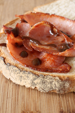 Freshly made bacon sandwich with brown sauce selective focus on the bacon