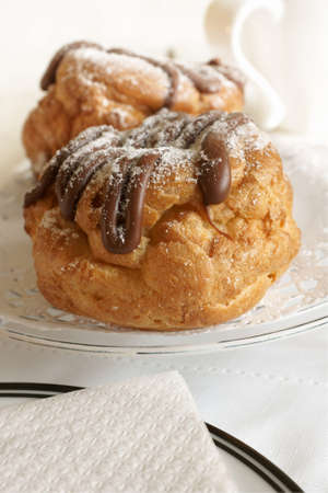 choux bun: Choux buns filled with cream and drizzled with chocolate and icing sugar