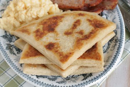 Irish potato farls or potato cakes with bacon and scrambled eggs