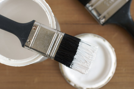 Painting and decorating a pot of white paint and brush Foto de archivo