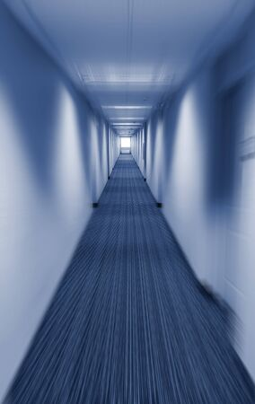 vanishing point: Long corridor vanishing point with applied motion blur filter in cold blue tint