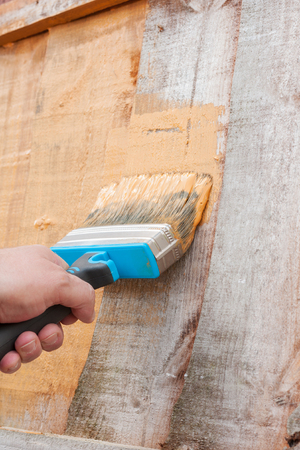 old tools: Painting a fence or a shed with wood preservative to protect it from the elements Stock Photo