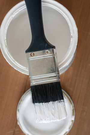 priming brush: Painting and decorating shallow focus top down view of a pot of white paint and brush