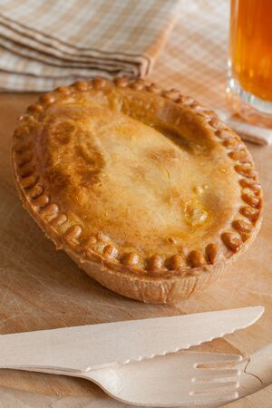 savoury: Savoury meat or steak pie takeaway with wooden cutlery Фото со стока