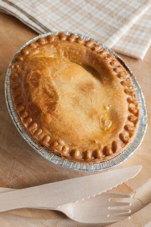 savoury: Savoury meat or steak pie takeaway in a foil tray with wooden cutlery