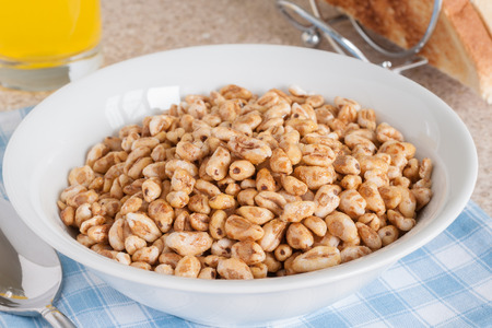 Honey coated puffed wheat breakfast cereal with orange juice and toast