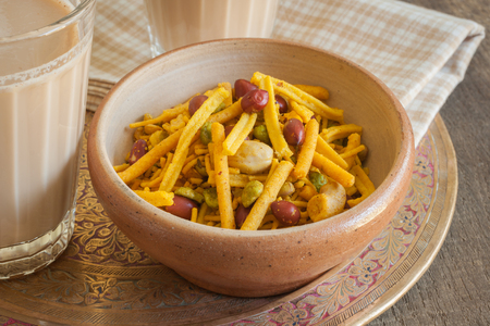 masala chai: A bowl of spicy Bombay Mix served with Indian Masala chai tea Stock Photo