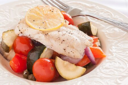 comida: Fish Provencal a French seafood dish of roasted vegetables and white fish fillet