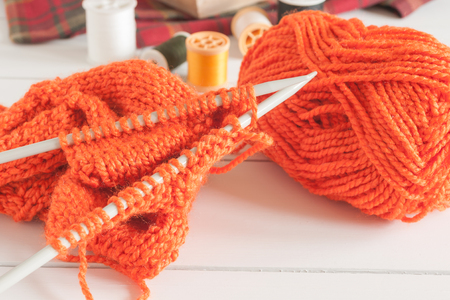 cardigan: Knitting a cardigan with needles and balls of orange wool a knitting or needlework concept