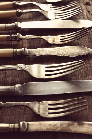 tarnish: Vintage knives and forks on an old wood table shot with shallow focus and vintage filter applied to image