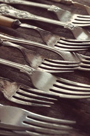 tine: Vintage forks on an aged wood table with a vintage filter