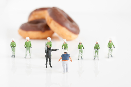 regulating: Police preventing an fat man from reaching donuts a public health obesity concept Stock Photo
