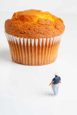 enormous: Overweight man looking up at an enormous muffin a portion size or obesity concept
