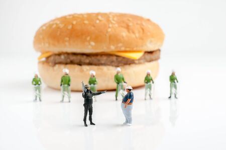 Tiny police preventing an overweight man from reaching a burger 版權商用圖片