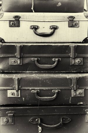 grungey: Stack of old battered suitcases with vintage style filter