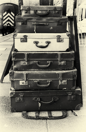 grungey: Stack of old vintage suitcases on a rail station