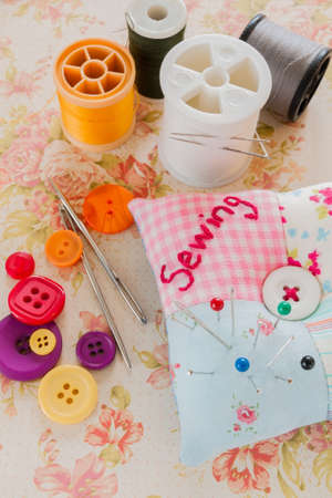 darning needle: Sewing needles threads and buttons with a pin cushion Stock Photo