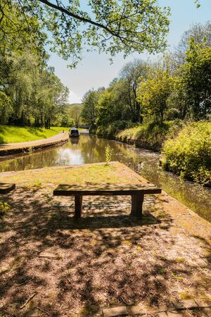 Shady tree lined view of the Llangollen canal with a narrowboat tied up on the bank