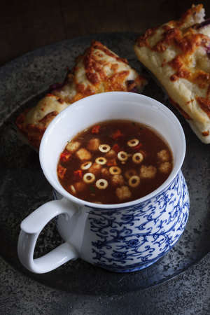 plate: A cup of Minestrone soup with mozarella and red onion focaccia bread shot with low key lighting Stock Photo
