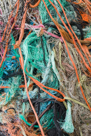 A tangled mess of fishing nets plastic rope washed up on beach Stock Photo