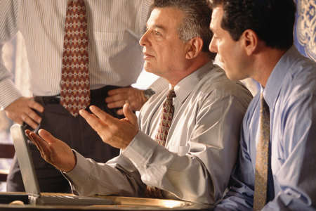 three businessmen with laptop computers