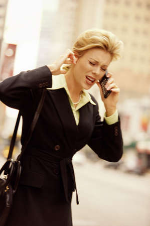 female executive using cell phone on downtown street