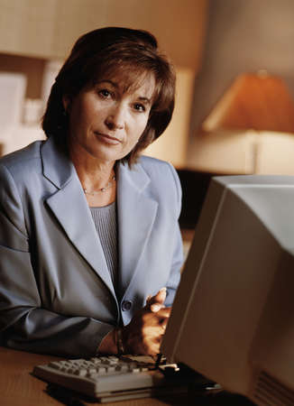 verticals: Portrait of businesswoman at her desk
