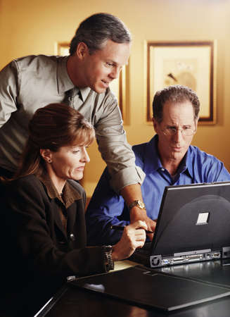 Group of co-workers looking at a laptop
