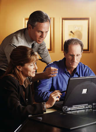 word processor: Group of co-workers looking at a laptop