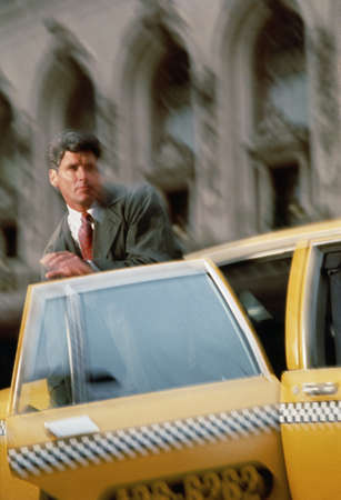 Businessman getting out of a yellow taxi cab