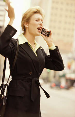 verticals: female executive on cell phone on downtown street Stock Photo