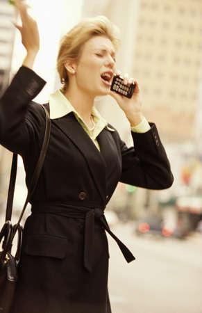 interactions: vrouwelijke executive op mobiele telefoon op straat downtown Stockfoto