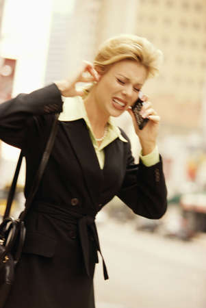 flip phone: female executive on cell phone on downtown street Stock Photo