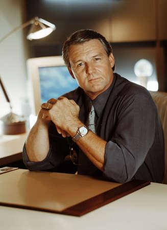 blissful: Portrait of businessman at his desk