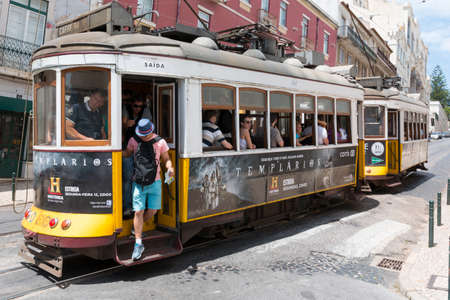 Lisbon, Portugal - August 5, 2014: Traditional yellow tram downtown Lisbon, Trams are used by everyone and also keep the traditional style of the historic center of Lisbon.