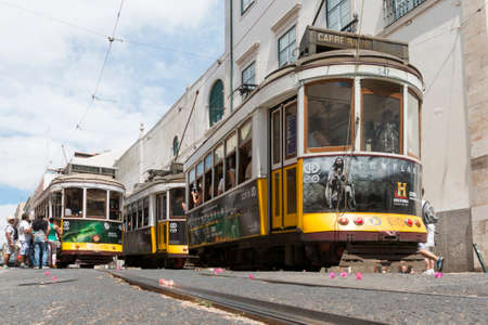 Lisbon, Portugal - August 9, 2014: Traditional yellow tram downtown Lisbon, Trams are used by everyone and also keep the traditional style of the historic center of Lisbon.