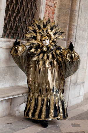 Venice, Italy – February 11 2012: Woman with typical venetian carnival costume at the Carnival of Venice. Shot in St. Marks Square. The Carnival of Venice is a annual festival held in Venice and is one of the most popular and appreciated carnival in th